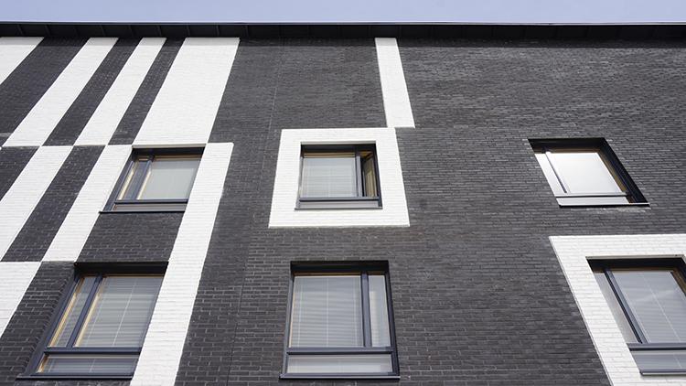 Osa ikkuna-aukoista on raamitettu valkoisella tiilellä.